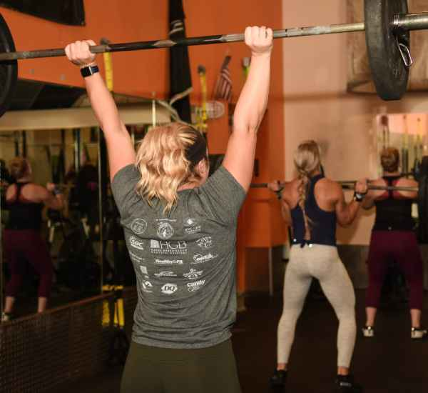 woman holding a weight bar above her head